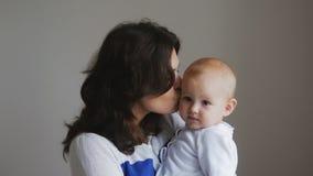 Mãe feliz nova que guarda sua criança recém-nascida Família em casa Mamã e bebê de sorriso bonitos junto Imagens de Stock Royalty Free