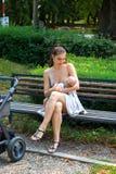 Mãe feliz nova que importa-se seu bebê em seus braços loving e que amamenta em público, sentando-se no banco de parque ao lado do imagens de stock