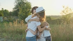 Mãe feliz que abraça as crianças, mulher com as três filhas na natureza video estoque