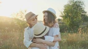 Mãe feliz que abraça as crianças, mulher com as três filhas na natureza filme