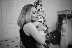 A mãe feliz que abraça a filha do bebê para a árvore de Natal ilumina-se no fundo fotos de stock royalty free