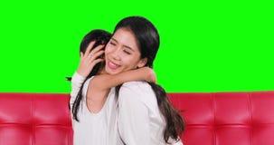 Mãe feliz que abraça sua filha no sofá filme