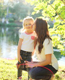 Mãe feliz que beija a criança da filha no verão Imagem de Stock