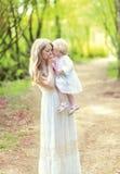 Mãe feliz que beija maciamente seu bebê que guarda sobre as mãos na mola imagens de stock
