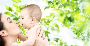 Mãe feliz que beija o bebê adorável Fotografia de Stock
