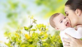 Mãe feliz que beija o bebê adorável imagem de stock