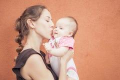 Mãe feliz que beija seu bebê no fundo da parede Fotografia de Stock Royalty Free