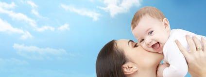 Mãe feliz que beija seu bebê sobre o céu azul imagem de stock
