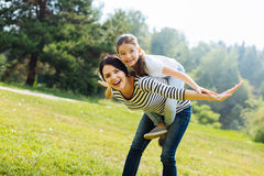 Mãe feliz que dá um passeio do reboque a sua filha foto de stock