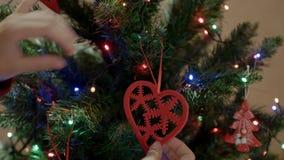 Mãe feliz que decotating a árvore do ano novo com a estrela do vermelho do brinquedo do Natal filme