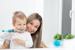 Mãe feliz que ensina a seu filho como cobrir os dentes fotos de stock royalty free