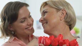 Mãe feliz que guarda flores, filha de inquietação que felicita a o 8 de março video estoque