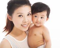 Mãe feliz que guarda o bebê de sorriso da criança Imagens de Stock Royalty Free