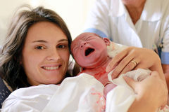 Mãe feliz que guarda seu bebê, segundos depois que deu um nascimento, n Imagem de Stock