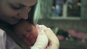 Mãe feliz que guarda um bebê recém-nascido em seus braços na sala video estoque