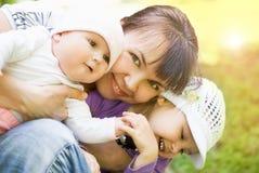 Mãe feliz que joga com as duas crianças pequenas Foto de Stock