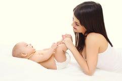 Mãe feliz que joga com o bebê bonito na cama Fotografia de Stock Royalty Free