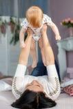 Mãe feliz que joga com o bebê que encontra-se na cama em casa Imagem de Stock