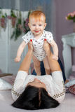 Mãe feliz que joga com o bebê que encontra-se na cama em casa Imagem de Stock Royalty Free