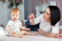 Mãe feliz que joga com o bebê que encontra-se na cama em casa Imagens de Stock Royalty Free