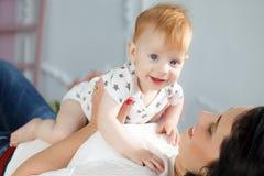 Mãe feliz que joga com o bebê que encontra-se na cama em casa Fotografia de Stock Royalty Free