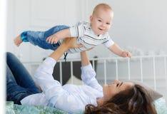 Mãe feliz que joga com o bebê que encontra-se na cama em casa Foto de Stock Royalty Free