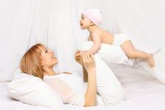 Mãe feliz que joga com o bebê que tem o divertimento junto na cama fotos de stock royalty free