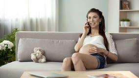 Mãe futura que fala no telefone celular e que toca na barriga, conversação com marido imagem de stock royalty free