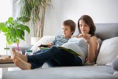 Mãe grávida dos jovens e seu menino, comendo a pizza saboroso em casa, w fotografia de stock royalty free