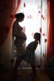 Mãe grávida feliz e sua filha pequena foto de stock royalty free