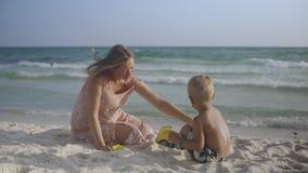A mãe grávida nova senta-se com seu filho na areia na praia que beija e que tem o divertimento no verão 4k video estoque