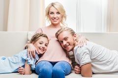 Mãe grávida que abraça o marido e a filha ao descansar no sofá em casa imagem de stock royalty free