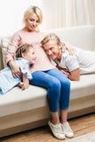 Mãe grávida que abraça o marido e a filha ao descansar no sofá em casa imagem de stock