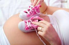 Mãe grávida que pleaying com sapatilhas do bebê ao encontrar-se na cama Imagens de Stock Royalty Free
