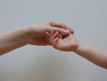 A mãe guarda a mão de seu bebê Foto de Stock