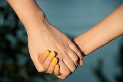 A mãe guarda a mão de sua filha Imagem de Stock