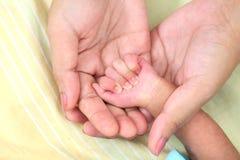 A mãe guarda a mão recém-nascida dos babys fotografia de stock royalty free