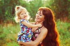 A mãe guarda o bebê em seus braços imagem de stock