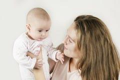 A mãe guarda o bebê em seus braços no fundo isolado imagens de stock