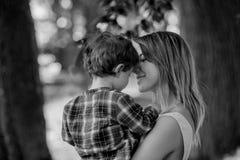 A mãe guarda o filho no as mãos em exterior imagens de stock royalty free