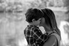 A mãe guarda o filho no as mãos em exterior imagem de stock