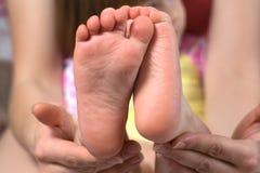 A mãe guarda os pés de uma jovem criança Foto de Stock