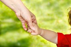 A mãe guarda seu bebê da mão Fotografia de Stock