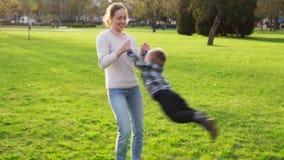 A mãe guarda seu filho pelos braços e pelos giros com ele no parque no por do sol filme