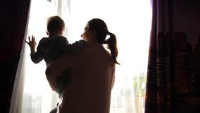 A mãe guarda uma criança na manhã perto da janela Cedo na manhã abrem as cortinas, os raios do sol passam filme