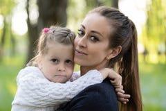 A mãe guarda uma menina em seus braços imagens de stock