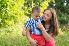A mãe implora o filho desagradado continuar o jogo Fotografia de Stock