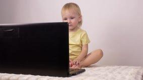 A mãe inclui desenhos animados no portátil de sua filha pequena, menina olha em um laptop, tecnologia filme