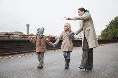 A mãe indica algo na distância às crianças Fotos de Stock Royalty Free