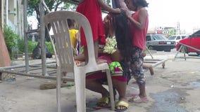 Mãe indigente que é cabelo preparado por suas crianças, implorando na porta portal da igreja vídeos de arquivo